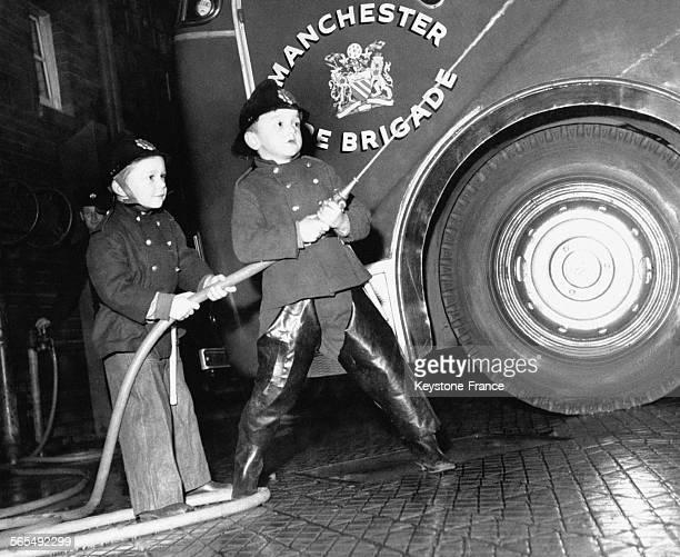Petits garçons vêtus de l'uniforme de pompier tirent sur la lance à incendie