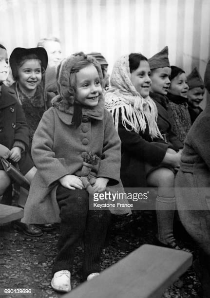 Petits spectateurs regardant le spectacle du Guignol des Buttes Chaumont à Paris France le 28 février 1940