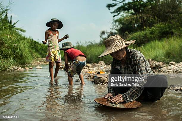 Petong pans for gold as her children play in the water on March 25 2014 in Lampang Thailand Thai villagers from Wang Nuea North of Thailand look for...