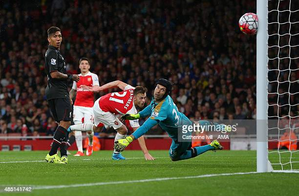 Petr Cech of Arsenal looks back as a shot from Philippe Coutinho of Liverpool hits the post during the Barclays Premier League match between Arsenal...