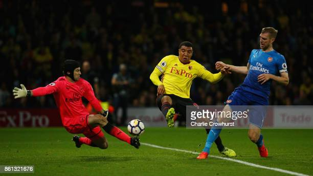 Petr Cech of Arsenal makes a save from Troy Deeney of Watford as Per Mertesacker of Arsenal looks on during the Premier League match between Watford...