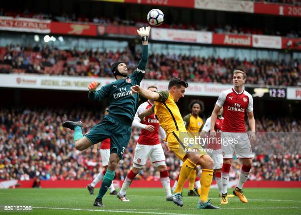 Petr Cech of Arsenal punches the ball while under pressure from Lewis Dunk of Brighton and Hove Albion during the Premier League match between...