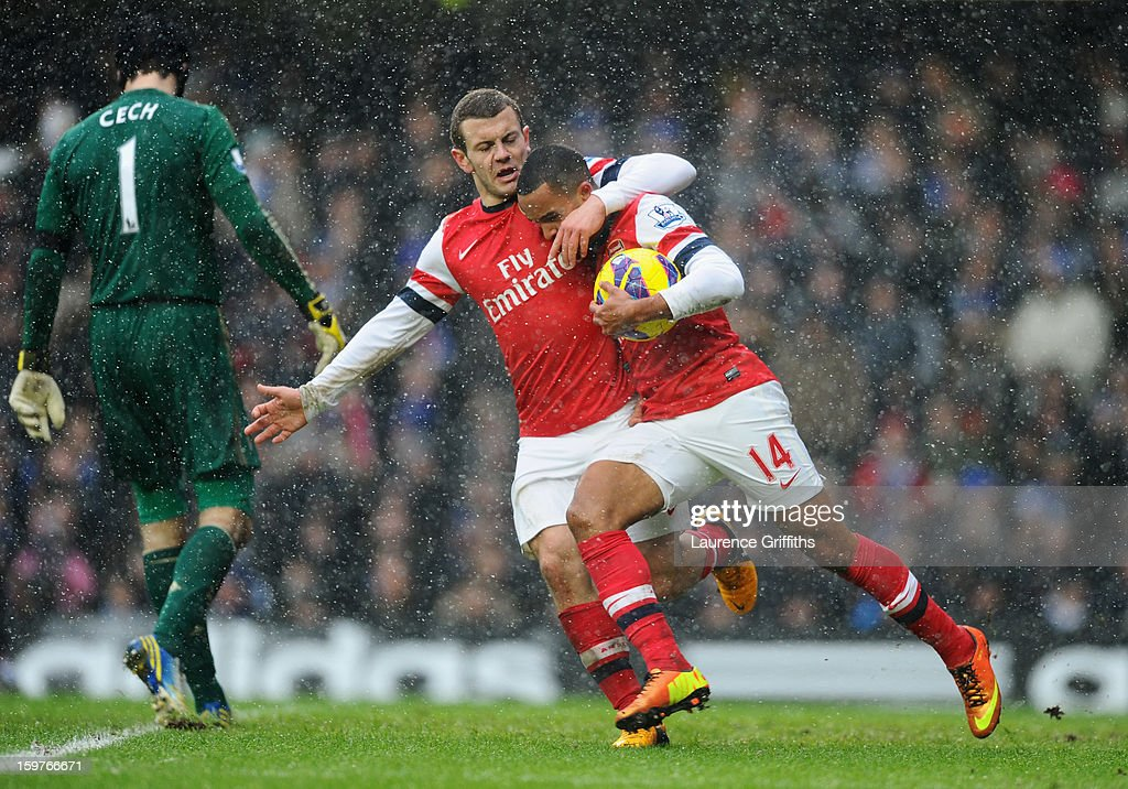 Petr Cech of Chelsea looks dejected as Theo Walcott of Arsenal (14) celebrates with Jack Wilshere of Arsenal as he scores their first goal during the Barclays Premier League match between Chelsea and Arsenal at Stamford Bridge on January 20, 2013 in London, England.