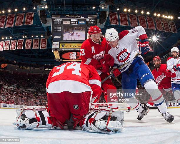 Petr Mrazek of the Detroit Red Wings covers the puck as teammate Pavel Datsyuk battles in front of the net with Michael McCarron of the Montreal...