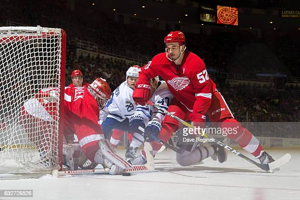 Petr Mrazek of the Detroit Red Wings looks to cover the puck as teammate Jonathan Ericsson battles with Leo Komarov of the Toronto Maple Leafs during...
