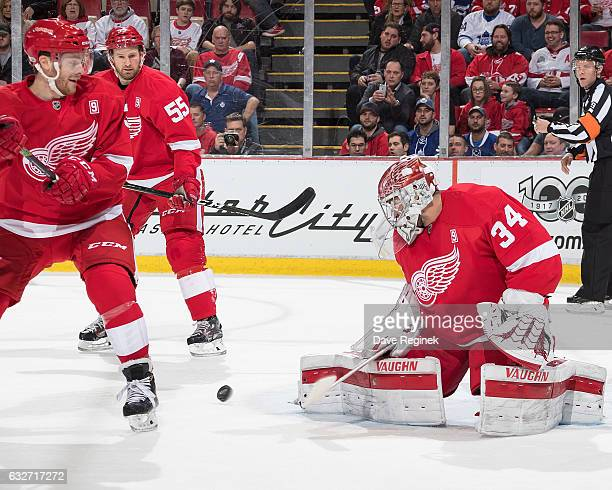 Petr Mrazek of the Detroit Red Wings makes a pad save while teammates Niklas Kronwall and Nick Jensen look for the rebound during an NHL game against...