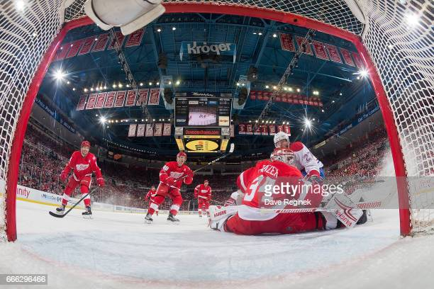 Petr Mrazek of the Detroit Red Wings makes a save as Alex Galchenyuk of the Montreal Canadiens skates in for the rebound during an NHL game at Joe...