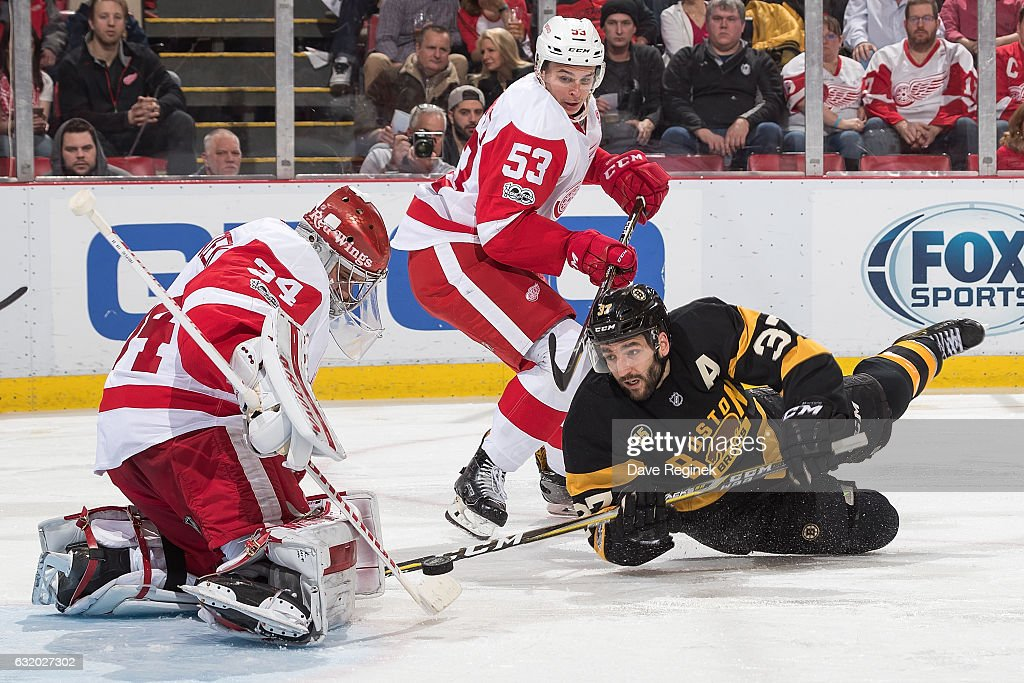 Petr Mrazek #34 of the Detroit Red Wings makes a save as teammate Alexey Marchenko #53 defends against Patrice Bergeron #37 of the Boston Bruins during an NHL game at Joe Louis Arena on January 18, 2017 in Detroit, Michigan.