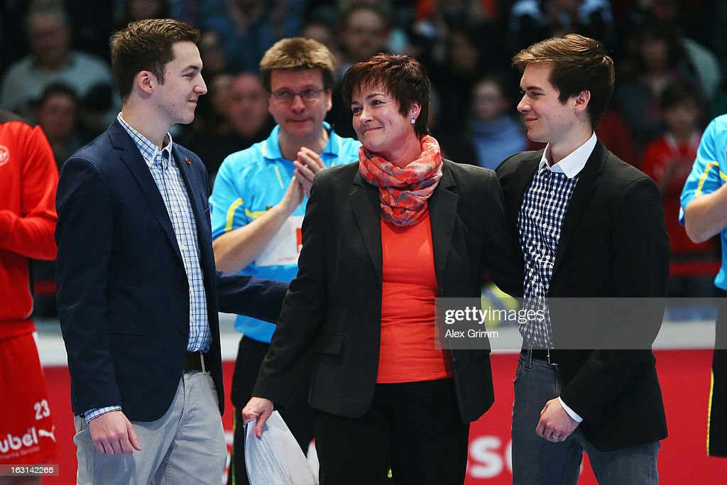 Petra Methe, widow of former referee Bernd Methe, who had died with his twin brother in a car accident, is hugged by her son and her nephew prior to a benefit match between the German national handball team and MT Melsungen at Rothenbach-Halle on March 5, 2013 in Kassel, Germany.
