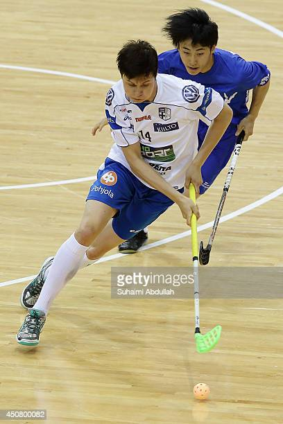 Petri Hakonen of Finland dribbles past Masato Wakamatsu of Japan during the World University Championship Floorball match between Japan and Finland...