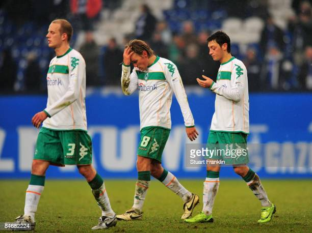 Petri Pasanen Clemens Fritz and Mesut Oezil of Bremen look dejected at the end of the Bundesliga match between FC Schalke 04 and Werder Bremen at the...