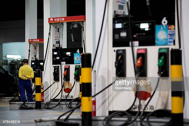 A Petrochina Co employee stands next to gas pumps at one of the company's gas stations in Hong Kong China on Tuesday March 18 2014 Petrochina the...