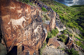 Ancient petroglyph of goats and people on the stone in open air museum Tanbaly at mountains sky background