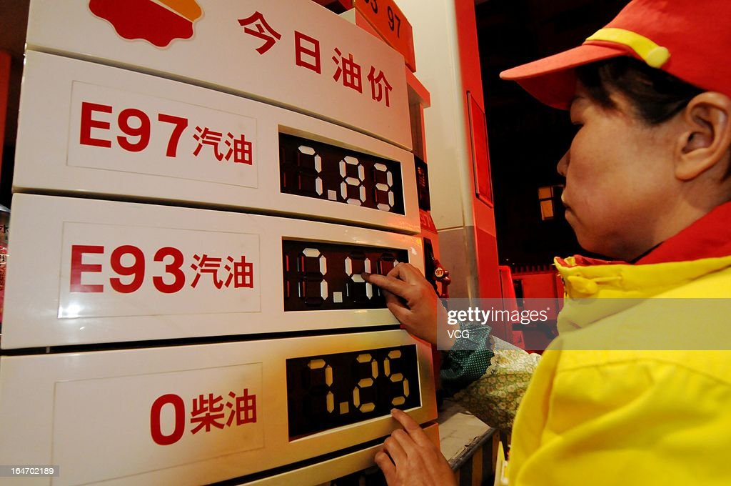 A petrol attendant changes the prices of gasoline and diesel at a gas station on March 27, 2013 in Luoyang, China. China cut the benchmark retail price for gasoline by 310 yuan (49.85 U.S. dollars) per ton and the price for diesel by 300 yuan per ton starting from Today.