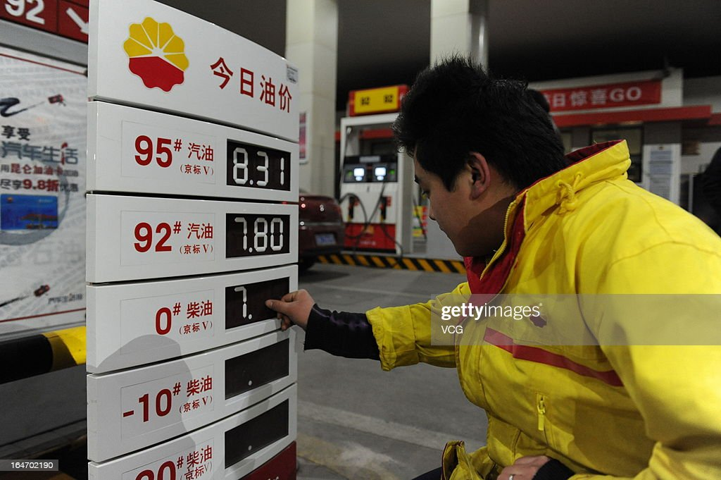 A petrol attendant changes the prices of gasoline and diesel at a gas station on March 27, 2013 in Beijing, China. China cut the benchmark retail price for gasoline by 310 yuan (49.85 U.S. dollars) per ton and the price for diesel by 300 yuan per ton starting from Today.