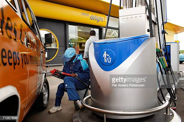 A petrol attendant fills a customers car during rush hour at a Sasol station on February 7 2006 in Soweto outside Johannesburg South Africa Sasol...