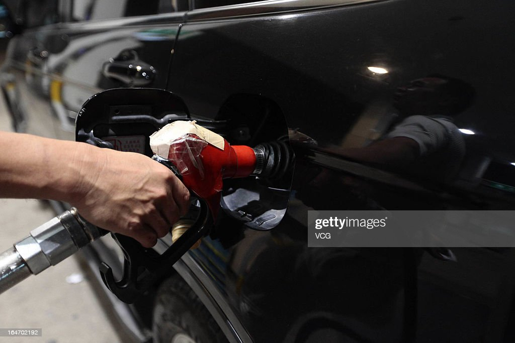 A petrol attendant fuels a vehicle at a gas station on March 27, 2013 in Sanya, China. China cut the benchmark retail price for gasoline by 310 yuan (49.85 U.S. dollars) per ton and the price for diesel by 300 yuan per ton starting from Today.