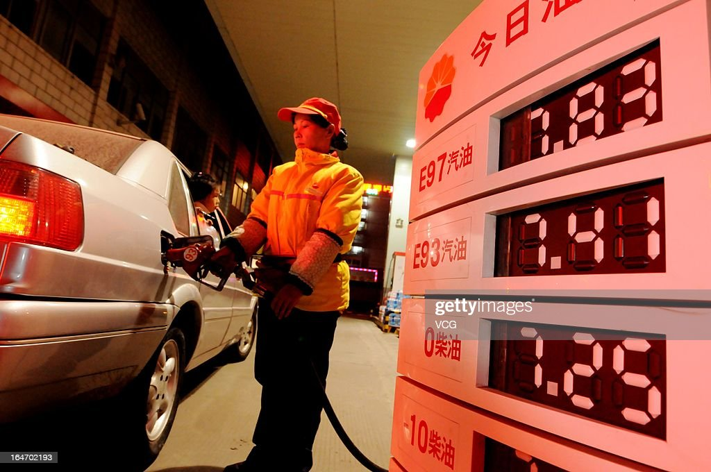 A petrol attendant fuels a vehicle at a gas station on March 27, 2013 in Luoyang, China. China cut the benchmark retail price for gasoline by 310 yuan (49.85 U.S. dollars) per ton and the price for diesel by 300 yuan per ton starting from Today.