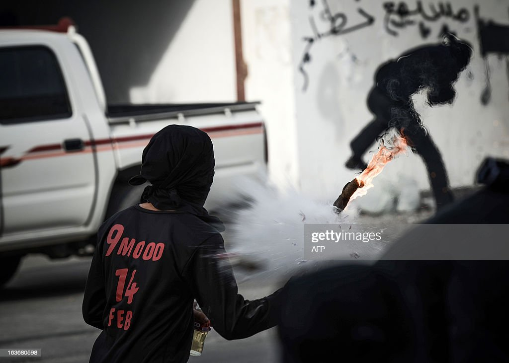 A petrol bomb explodes in the hand of a protester after being targeted by a tear gas canister fired by Bahraini police during an anti-government demonstration in the village of Sanabis, West of Manama, on March 14, 2013. Bahraini police clashed with youths protesting against the deployment into a third year of a Gulf military force that backed Manama's bid to crush a Shiite-led uprising, witnesses said.