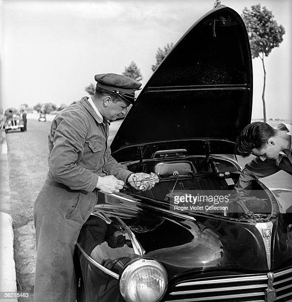 Petrol pump attendant checking the oil level of a 203 Peugeot in a BP service station France about 1952