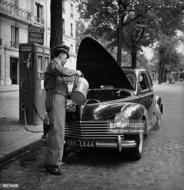 Petrol pump attendant filling up the water tank of a 203 Peugeot in a BP service station France about 1952