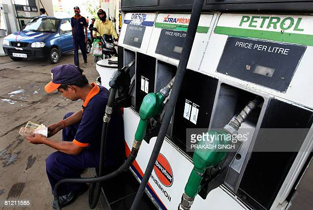 A petrol pump employee counts the currency notes while waiting for vehicles at a petrol and diesel station in New Delhi on May 23 2008 Petroleum...