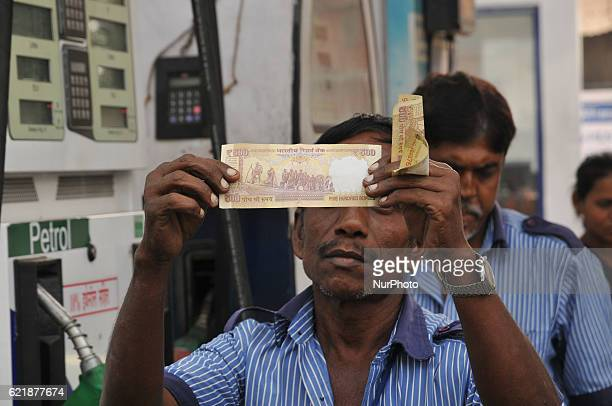 HP Petrol Pump worker look on Indian Currency 500 Rupees HP PETROL PUMP dealers not to accept Rs 500 and 1000 Indian currency A closeup view of a...