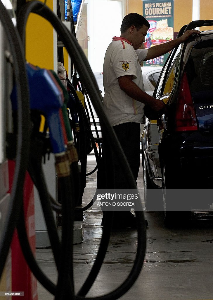 A petrol station worker refuels a car on January 30 , 2013 in Rio de Janeiro, Brazil. The price of the fuel in Brazil increased in 6,5% at the refinery, meaning 4,6% to the customers at the petrol pump.