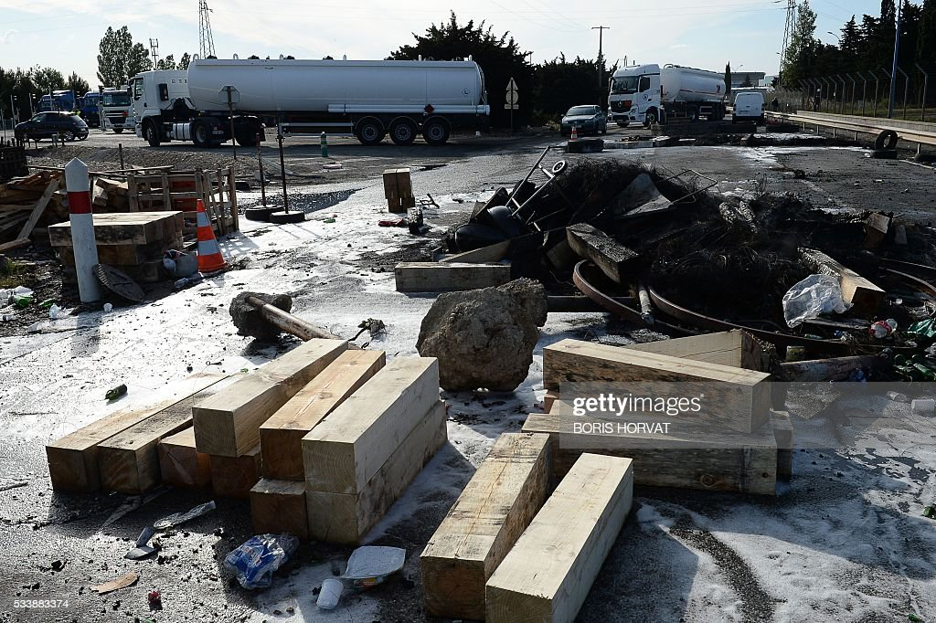 Petrol tankers are driven past the dismantled drive past a dismantled barricade of protesting French CGT unionsists in front of the Esso oil refinery in Fos-sur-Mer, southeastern France, on May 24, 2016, after police evacuated the site which was blockaded by protesters opposed to government labour reforms. Petrol shortages caused long tailbacks of motorists in parts of France on May 23 as protesters angry over government labour reforms blockaded some of the country's oil refineries and fuel depots. The action was the latest in three months of strikes and protests against the reform, which has set the Socialist government against some of its traditional supporters and sometimes sparked violence. HORVAT