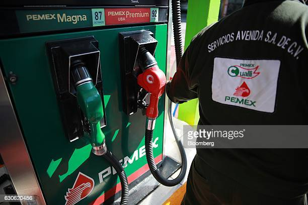 A Petroleos Mexicanos employee grabs a fuel pump at the company's gas station in Mexico City Mexico on Wednesday Dec 28 2016 Mexico will raise...