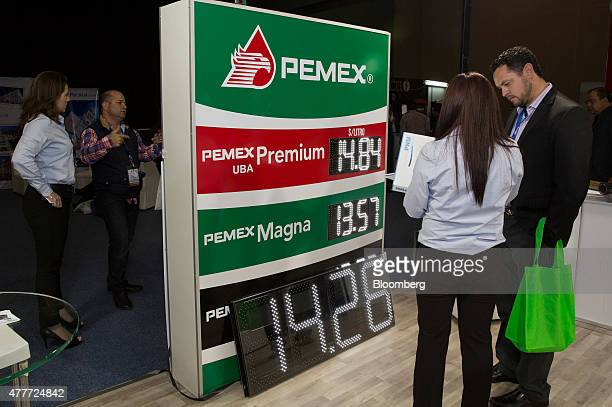 Petroleos Mexicanos gas station signs are displayed as attendees speak with vendors during the Onexpo 2015 convention and expo in Mexico city Mexico...