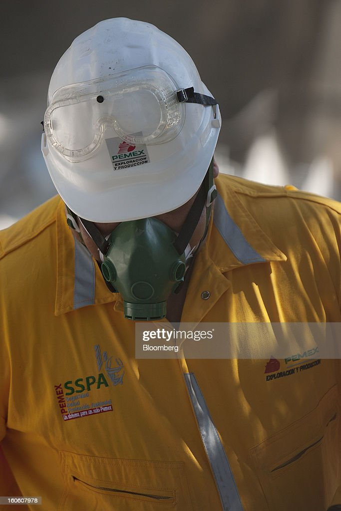 A Petroleos Mexicanos (Pemex) worker looks at debris at the Petroleos Mexicanos (Pemex) administrative building in Mexico City, Mexico, on Sunday, Feb. 3, 2013. The search for the cause of a blast that destroyed three floors of a building at Pemex' headquarters and killed at least 34 people entered a fourth day, as investigators toiled ahead of a self-imposed deadline for finding an answer. Photographer: Susana Gonzalez/Bloomberg via Getty Images