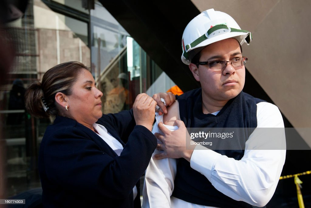 A Petroleos Mexicanos (Pemex) worker receives a vaccination shot from a nurse during cleanup operations at the company's headquarters building in Mexico City, Mexico, on Tuesday, Feb. 5, 2013. Mexican authorities said a buildup of gas led to the blast last week that killed 37 people at Petroleos Mexicanos's headquarters, the first official attempt to explain the nation's deadliest explosion since 2006. Photographer: Susana Gonzalez/Bloomberg via Getty Images