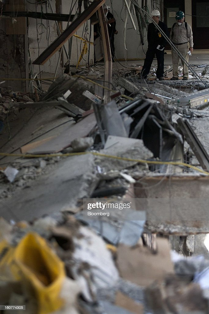 Petroleos Mexicanos (Pemex) workers inspect the damage at company headquarters in Mexico City, Mexico, on Tuesday, Feb. 5, 2013. Mexican authorities said a buildup of gas led to the blast last week that killed 37 people at Petroleos Mexicanos's headquarters, the first official attempt to explain the nation's deadliest explosion since 2006. Photographer: Susana Gonzalez/Bloomberg via Getty Images