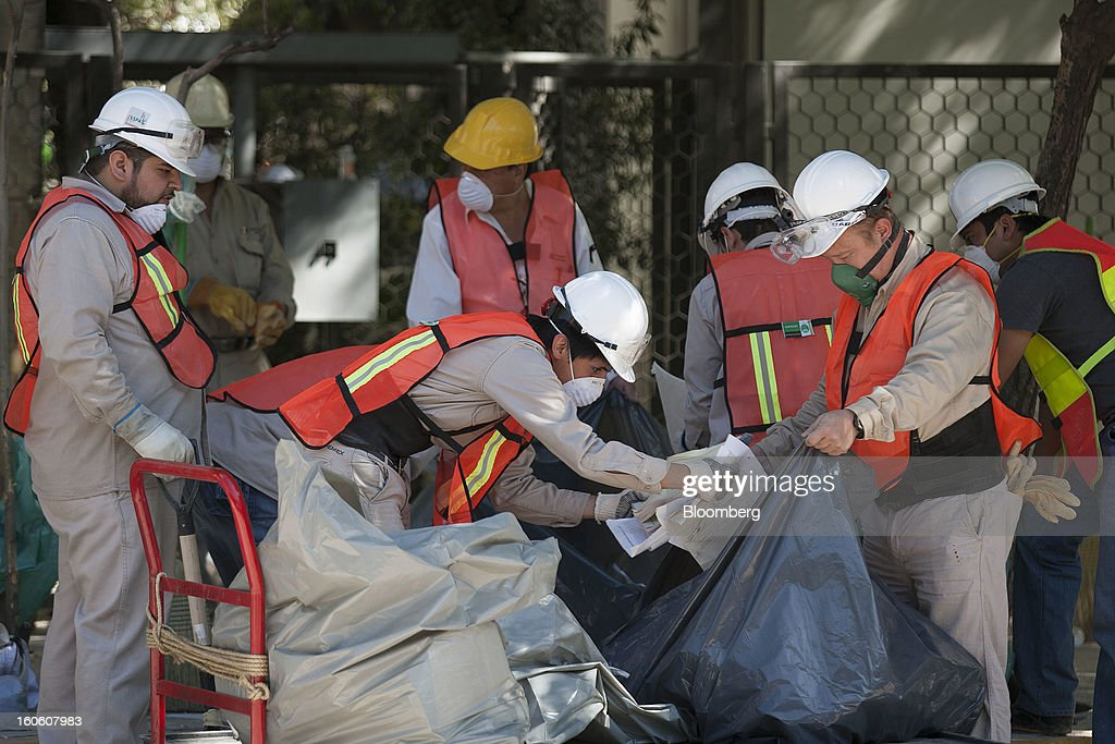 Petroleos Mexicanos (Pemex) workers place recovered documents into a plastic bag at the Petroleos Mexicanos (Pemex) administrative building in Mexico City, Mexico, on Sunday, Feb. 3, 2013. The search for the cause of a blast that destroyed three floors of a building at Pemex' headquarters and killed at least 34 people entered a fourth day, as investigators toiled ahead of a self-imposed deadline for finding an answer. Photographer: Susana Gonzalez/Bloomberg via Getty Images