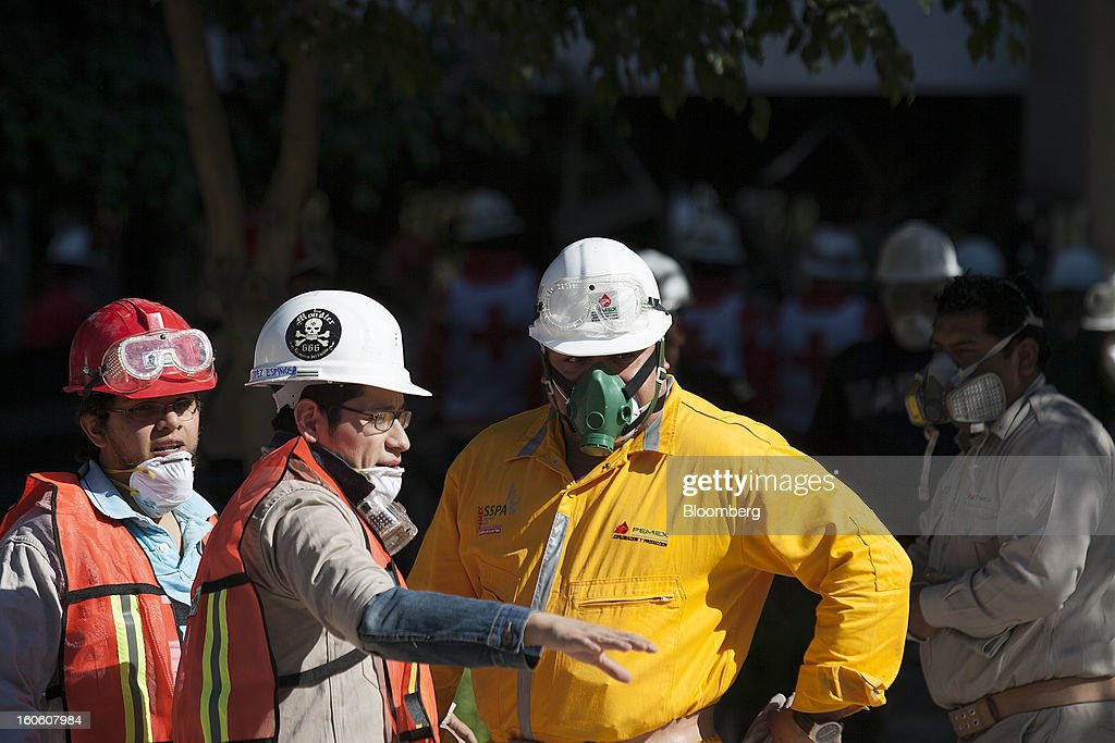 Petroleos Mexicanos (Pemex) workers talk about the debris at the Pemex administrative building in Mexico City, Mexico, on Sunday, Feb. 3, 2013. The search for the cause of a blast that destroyed three floors of a building at Pemex' headquarters and killed at least 34 people entered a fourth day, as investigators toiled ahead of a self-imposed deadline for finding an answer. Photographer: Susana Gonzalez/Bloomberg via Getty Images