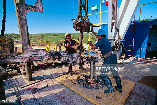 Petroleum Workers Moving a Drill