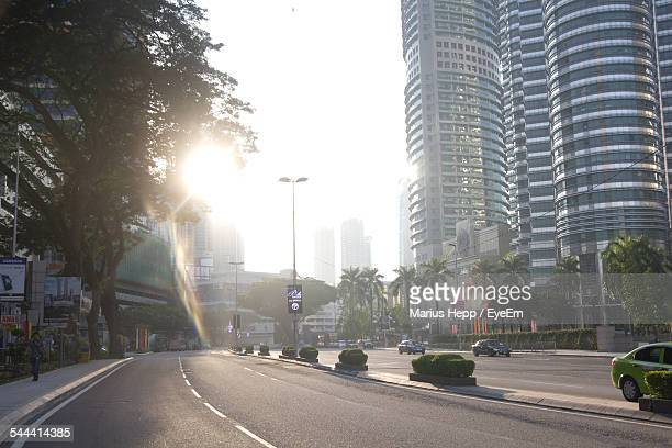 Petronas Towers By City Street Against Clear Sky