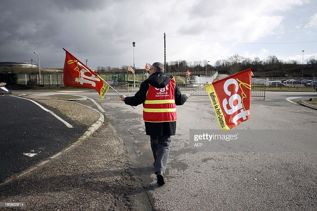 A Petroplus worker holds CGT trade union flags during a protest outside the Petroplus oil refinery, on February 6, 2013 in Petit-Couronne, northwestern France. Petroplus bankrupt oil refinery northwest of Paris has attracted five offers, with the two most serious bids coming from Egypt and Switzerland, the French ministry of industrial regeneration said on February 5, as the Petroplus site that employs 470 people focused French anxiety over plant closures. AFP PHOTO / CHARLY TRIBALLEAU