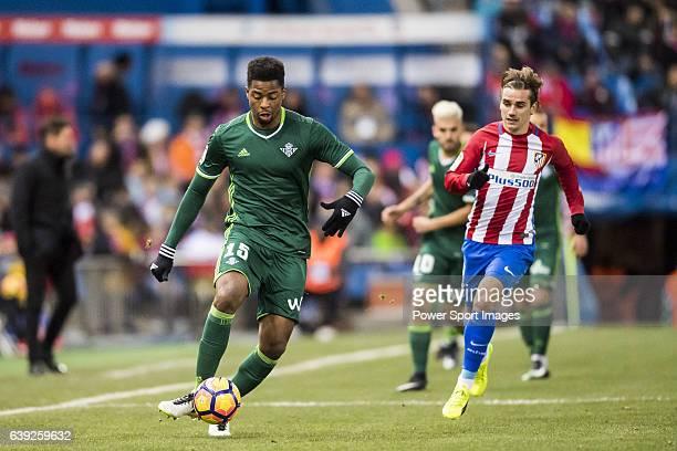 Petros Matheus dos Santos Araujo of Real Betis Balompie is followed by Antoine Griezmann of Atletico de Madrid during their La Liga 201617 match...
