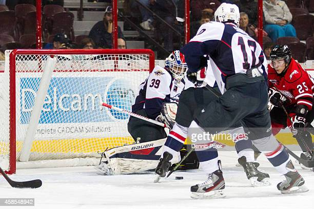 Petrus Palmu of the Owen Sound Attack drives the net against Alex Fotinos of the Windsor Spitfires on November 6 2014 at the WFCU Centre in Windsor...