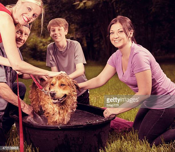 Pets: Multi-generation family gives pet dog a bath. Backyard. Summer.