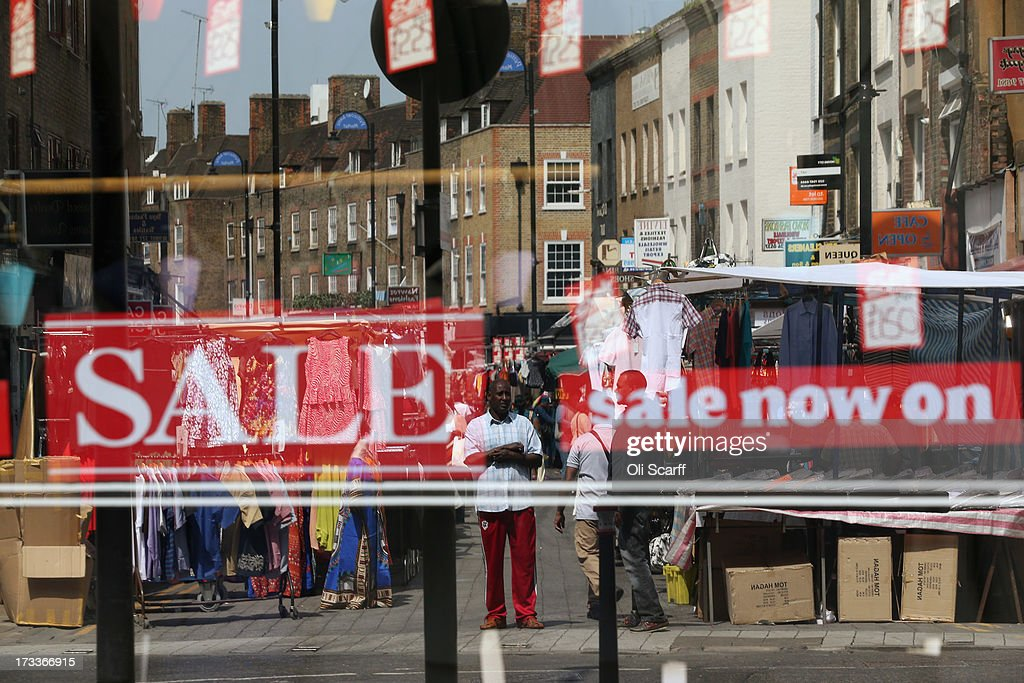 Petticoat Lane Market is reflected in the window of an adjacent suit shop on July 12, 2013 in London, England. Petticoat Lane Market is a historic clothing market in East London with records of trading on the site dating from around the year 1600.