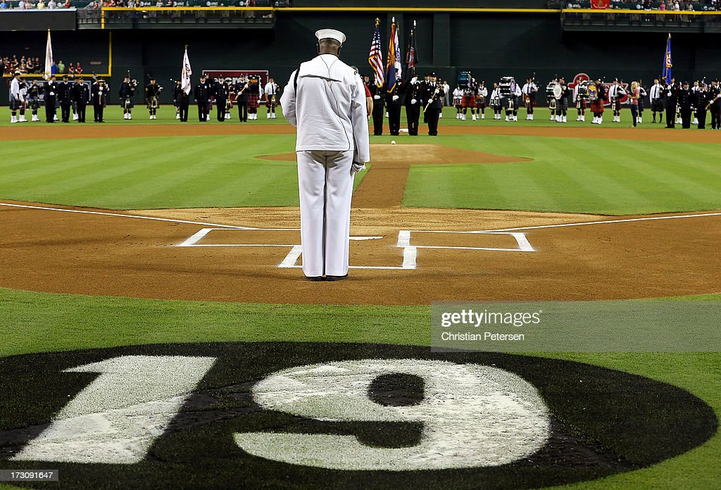 Petty Officer Steven Powell - US Navy and the Arizona Joint Fire Fighters Honor Guard stand in silence to honor of the 19 Granite Mountain Interagency Hotshot Crew firefighters who died battling a fast-moving wildfire near Yarnell, AZ before the MLB game between the Arizona Diamondbacks and the Colorado Rockies at Chase Field on July 5, 2013 in Phoenix, Arizona.
