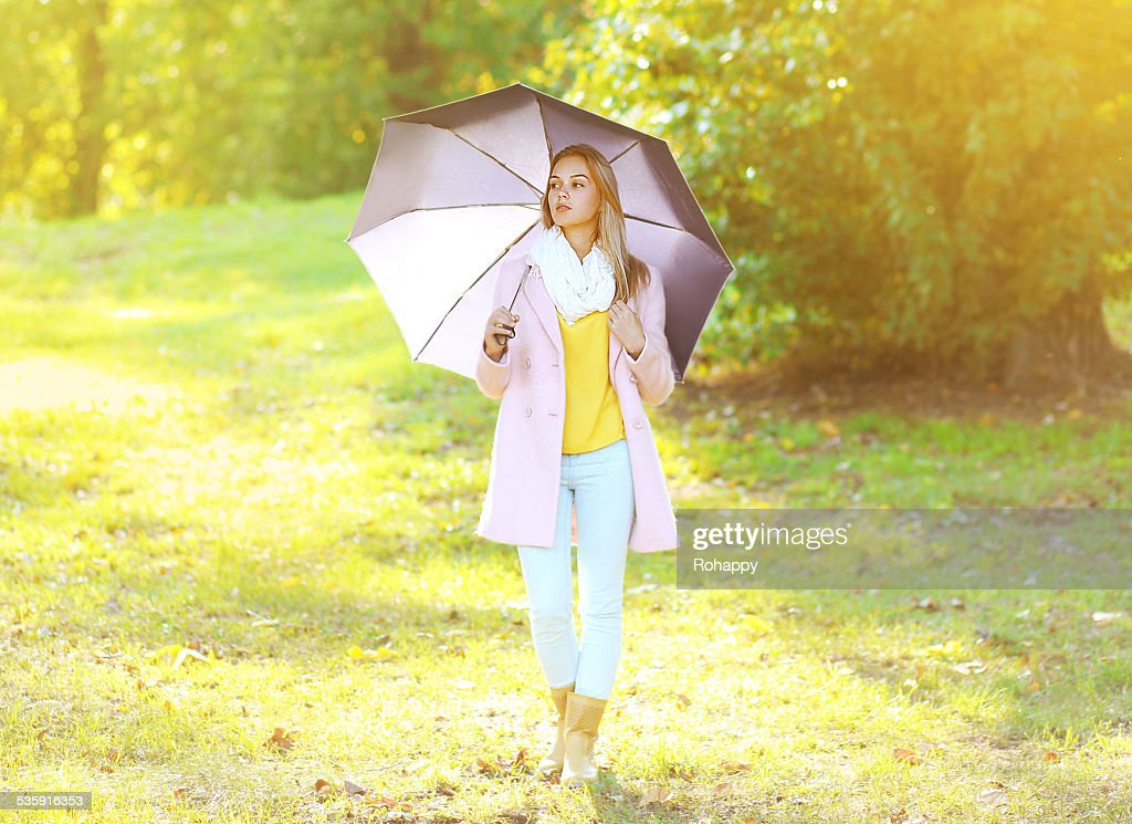 Petty sensual mujer con sombrilla en sunny autumn day : Foto de stock