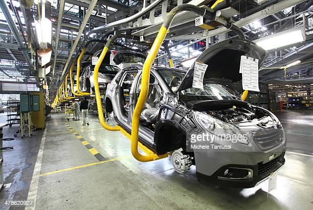 Peugeot 2008 SUVs car sit on a conveyor at the PSA Peugeot Citroen assembly plant on March 14 2014 in Mulhouse France Chinese automaker Dongfeng is...