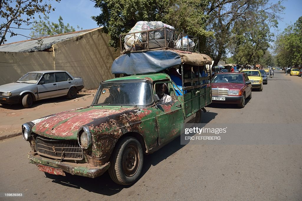 A Peugeot 404 pick-up used as a taxi is pictured on January 21, 2013 in a street of Bamako. French and Malian troops recaptured the key towns of Diabaly and Douentza on Monday in a major boost in their drive to rout Al Qaeda-linked rebels holding Mali's vast arid north. AFP/PHOTO ERIC FEFERBERG