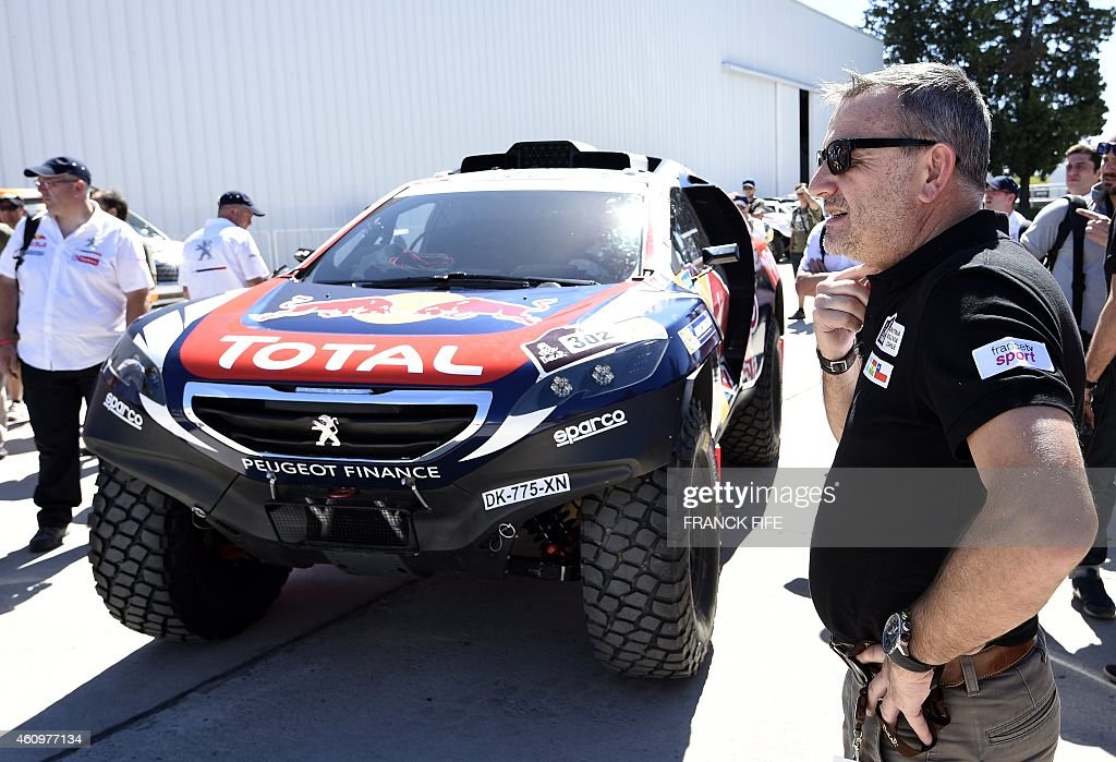 Peugeot's driver Cyril Despres of France passes next to Dakar Rally director Etienne Lavigne in Buenos Aires Argentina on January 2 ahead of the 2015...