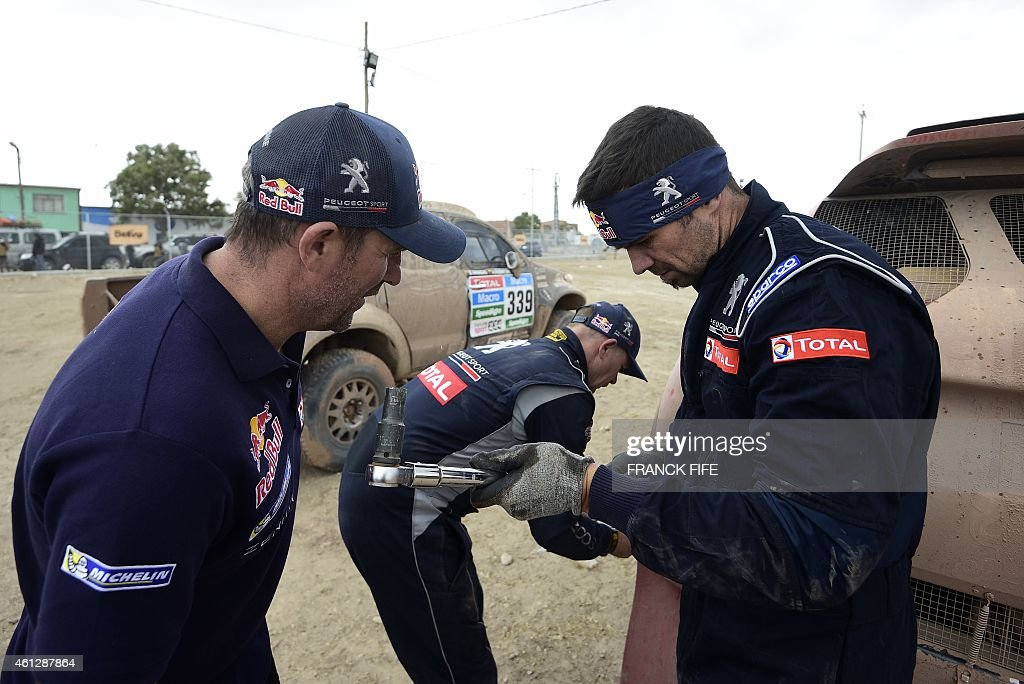 Peugeot's driver Cyril Despres of France speaks with Peugeot's driver Stephane Peterhansel of France after the Stage 7 of the Dakar 2015 between...
