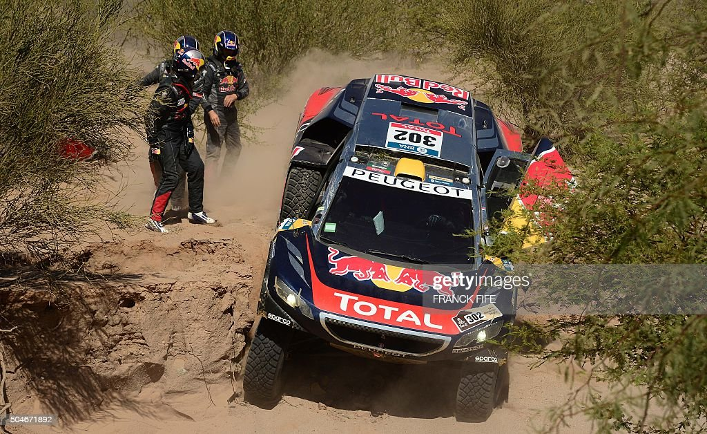 TOPSHOT Peugeot's driver Stephane Peterhansel and codriver Jean Paul Cottret are helped by Peugeot's driver Cyril Despres and codriver David Castera...